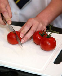 Pupil chopping tomatoes